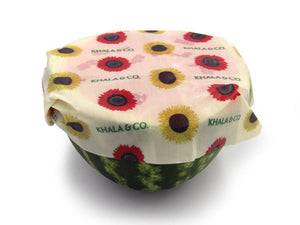 Sustainable Vegan Wax wrap in the size Large covering the cut side of a juicy watermelon, featuring the print Among the Sunflowers, which is a cheerful collection of traditional yellow and brilliant red sunflowers accompanied by the Khala & CO logo.