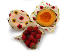 Load image into Gallery viewer, Sustainable Vegan Wax wrap 3 Medium pack in action, covering the cut sides of ripe canteloupe and folded into a bag to enclose delicious ruby red strawberries as an eco-friendly alternative to plastic wrap or bags. All wraps are in the print Among the Sunflowers, which is a cheerful collection of traditional yellow and brilliant red sunflowers accompanied by the  Khala & CO logo in green.