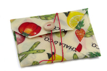 Load image into Gallery viewer, Sustainable Vegan Wax Sandwich wrap in the print Harvest folded flat on a white background, tying shut with red string and wooden button. Used as an eco-friendly alternative to single use plastic bags, and the print Harvest lends some personal flair with the cheerful and brightly painted vegetables cascading down the 100% organic hemp cotton blend fabric accompanied by the Khala & CO logo.