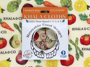 Sustainable Vegan Wax Wrap Sandwich wrap in the print Harvest in its recyclable packaging on a background of the featured print. Harvest has bright and realistic vegetables cascading down a 100% organic hemp cotton fabric background accompanied by the Khala & CO logo. Ties shut with a red string and wooden button.