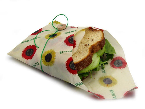 Sustainable Vegan Wax Sandwich wrap in the print Among the Sunflowers in action, enclosing a seedy bread sandwich with a green string and wooden button as an alternative to a single use plastic bag. Re-usable, durable, and eco-friendly, this wrap will last over a year, making it a great addition to your Zero Waste lifestyle! Among the Sunflowers is a cheerful collection of traditional yellow and brilliant red sunflowers accompanied by the Khala & CO logo.