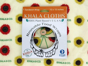 Sustainable Vegan Wax wrap Sandwich wrap in the print Among the Sunflowers in its recyclable packaging on a background of the featured print. Among the Sunflowers is a cheerful collection of traditional yellow and brilliant red sunflowers accompanied by the Khala & CO logo in green. Ties shut with a green string and wooden button.