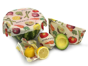 Sustainable Vegan Wax wrap Combo pack in action, covering cut sides of fresh produce or folded into bags as an eco-friendly alternative to plastic wrap and bags. All compostable wraps feature the print Harvest, which has realistically rendered and brightly colored vegetables cascading down the 100% organic hemp cotton blend fabric accompanied by the Khala & CO logo.
