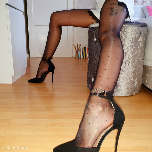 front view of lady wearing sheer black shiny polka dot pantyhose with black high heels