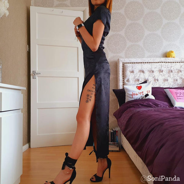 side view of lady wearing black satin qipao with split sides showing off her leg in black high heels