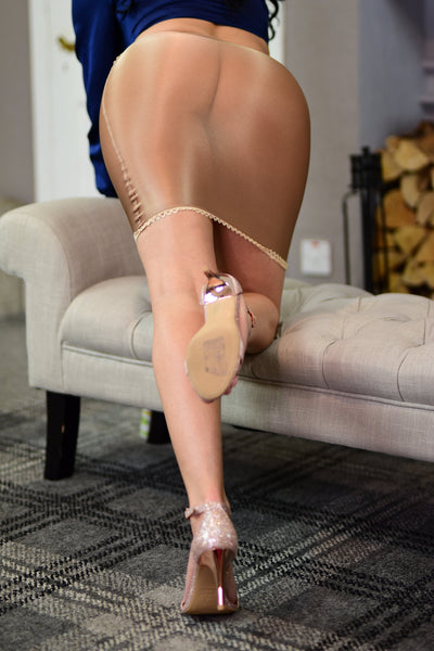 back view of lady wearing blue satin blouse with beige color nylon skirt with cream high heel