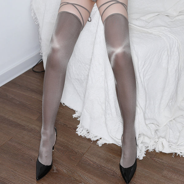 Grey thigh high stockings featuring shiny nylon and attached straps.