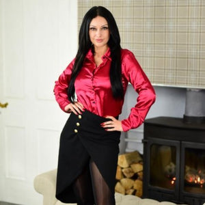 cassie clarke wearing a maroon color button down satin blouse with black skirt and black glossy pantyhose