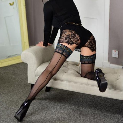 back view of lady wearing sheer peacock top thigh high stockings with black back seam