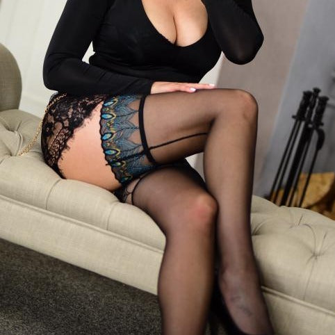 front side view of lady wearing sheer peacock top thigh high stockings with black back seam