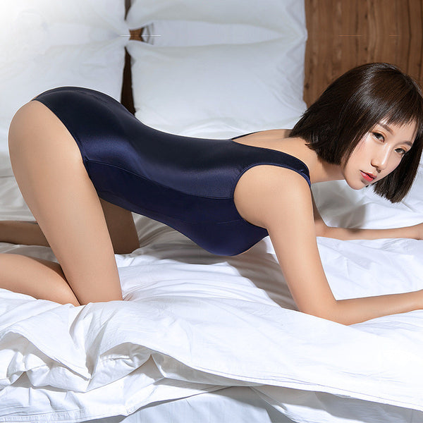 side view of lady bending over wearing a blue color wet look bodysuit feauring a scoop neckline, thick shoulder straps, a zipper closure crotch and a cheeky cut back.
