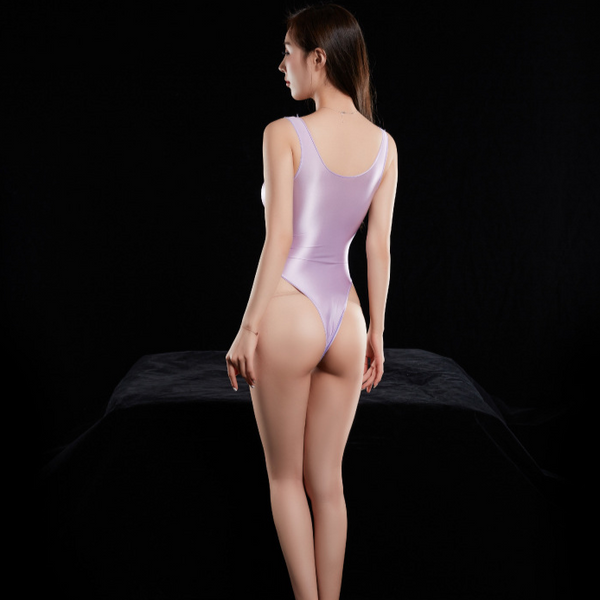 Purple wet look bodysuit featuring a scoop neckline, thick shoulder straps, arousing smooth to the touch fabric, high cut sides and a thong cut back.