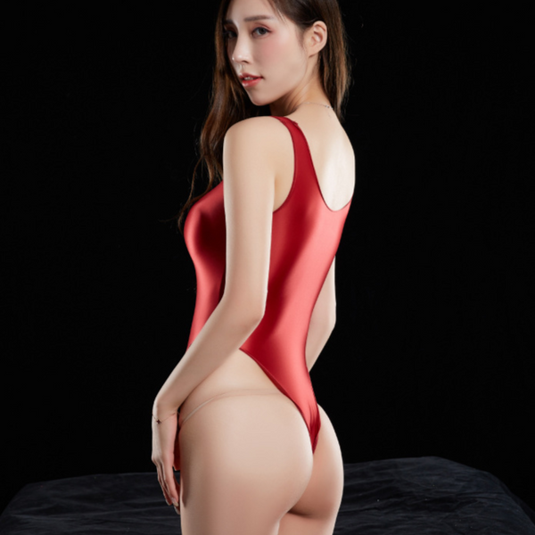 Red wet look bodysuit featuring a scoop neckline, thick shoulder straps, arousing smooth to the touch fabric, high cut sides and a thong cut back.