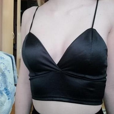 black satin bralette featuring a soft cups, spaghetti straps and plunging V-neckline, hook and eye closure.