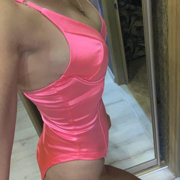 side view of lady wearing pink color satin bodysuit with plunging neck line and adjustable shoulder straps