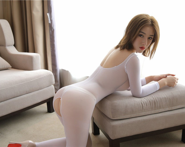 back view of lady wearing white color bodystocking, featuring long sleeves, scoop neck and an open crotch.