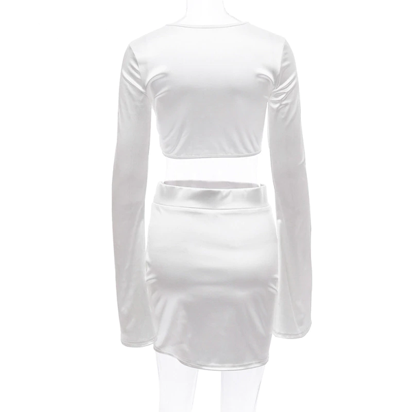 back view of white satin crop top with long sleeves, scoop neckline and a matching mini skirt.