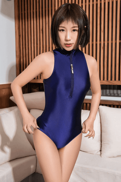 front view of lady wearing a blue wet look bodysuit featuring a high neckline, a front zipper closure, and a cheeky cut back.