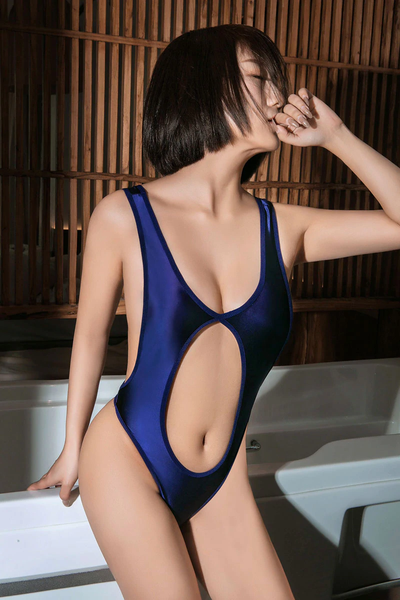 front view of lady wearing a blue color wet look bodysuit featuring a low cut keyhole, a scoop neckline, thick shoulder straps, and a thong cut back.