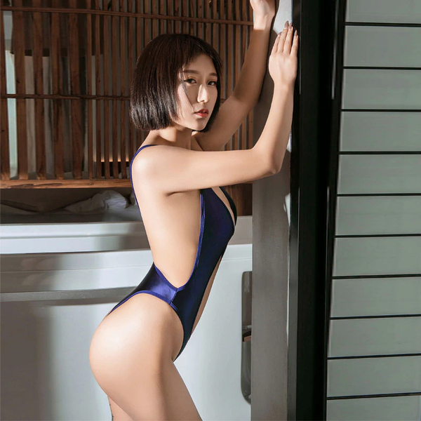 side view of lady wearing a blue color wet look bodysuit featuring a low cut keyhole, a scoop neckline, thick shoulder straps, and a thong cut back.