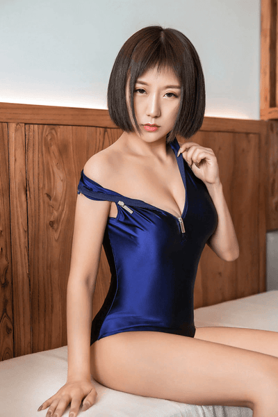 front view of lady wearing a blue blue wet look bodysuit featuring a high neckline, a front zipper closure, and a cheeky cut back.