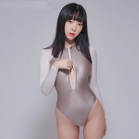front view of lady wearing ash wet look bodysuit featuring front zipper closure, long sleeves, high cut sides and a cheeky cut back.