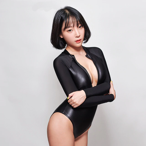 front view of lady wearing black wet look bodysuit featuring front zipper closure, long sleeves, high cut sides and a cheeky cut back.