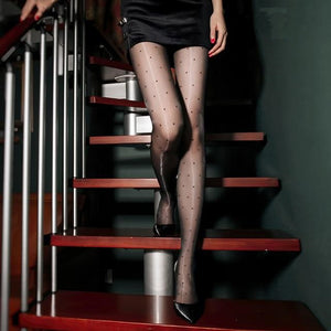 front view of lady wearing black color shiny sheer pantyhose with polka dot prints with black shiny high heels