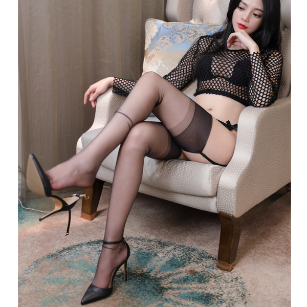 front view of lady wearing fishnet long sleeve top with black bra, black sheer thigh high stocking and black high heels