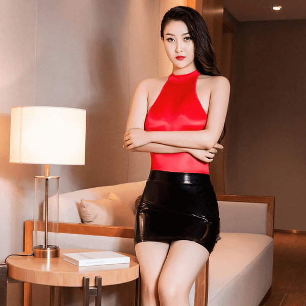 front view of lady wearing red sheer shiny bodysuit with black PU shiny mini skirt