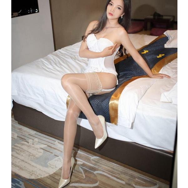 front view of lady wearing white corset top with beige shiny lace thigh high stocking with white high heels