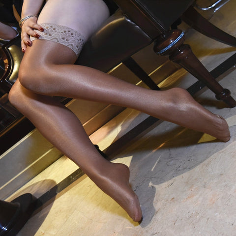 side view of lady wearing brown color oil shine thigh high stockings with floral overlay thigh band showing off her feet