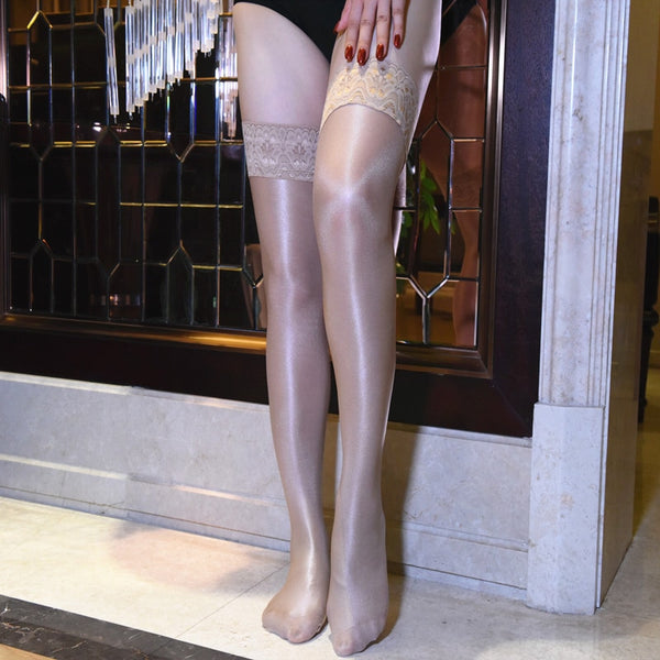 front view of lady wearing beige color oil shine thigh high stockings with floral overlay thigh band showing off her feet