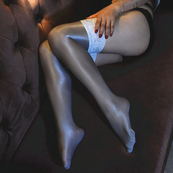 side view of lady wearing grey color oil shine thigh high stockings with floral overlay thigh band showing off her feet