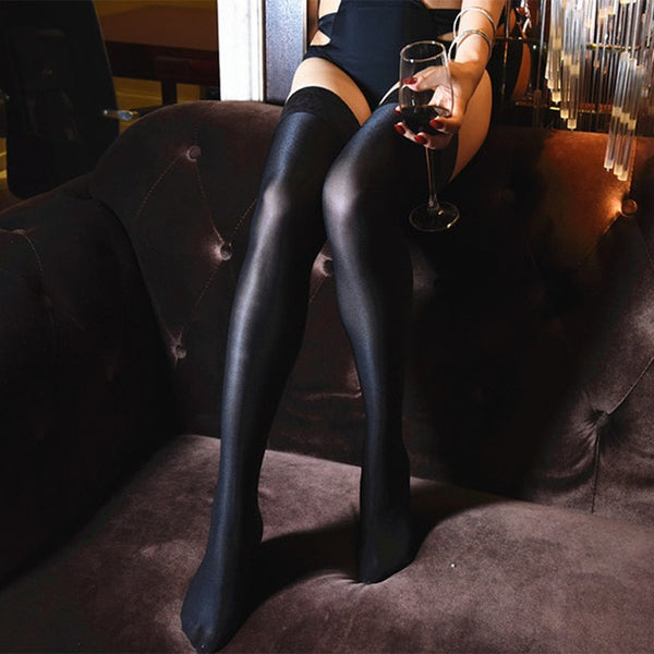 side view of lady wearing black color oil shine thigh high stockings with floral overlay thigh band showing off her feet