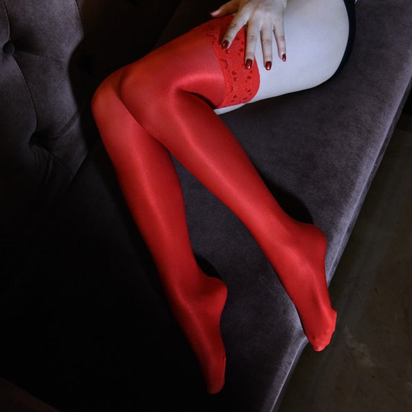 side view of lady wearing red color oil shine thigh high stockings with floral overlay thigh band showing off her feet