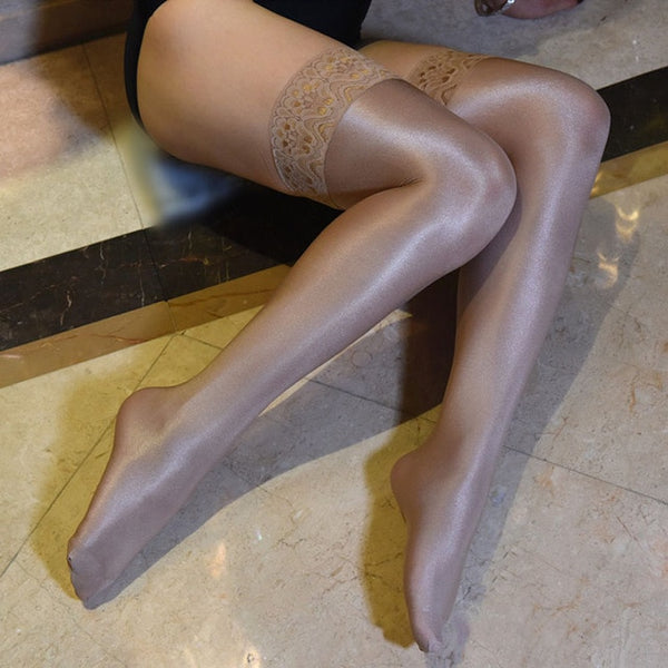 side view of lady wearing beige color oil shine thigh high stockings with floral overlay thigh band showing off her feet