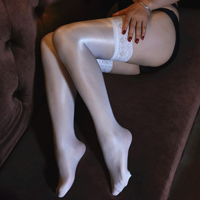 side view of lady wearing white color oil shine thigh high stockings with floral overlay thigh band showing off her feet