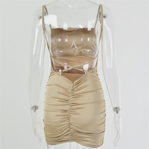 Champagne satin mini dress featuring spaghetti straps, adjustable back straps, square neck line, open side panel and a low cut back.