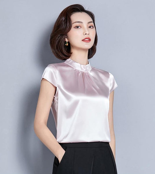 Pink satin top featuring short sleeves, a high neck line, and a fitted silhouette.