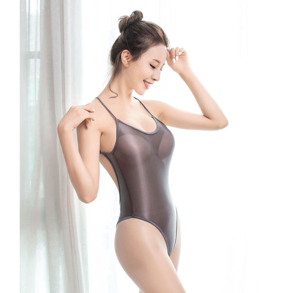 front view of lady wearing grey sheer bodysuit featuring a scoop neckline, spaghetti straps, high cut sides and a cheeky cut back.
