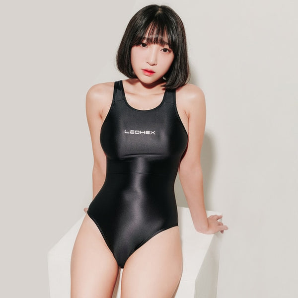front view of lady wearing black wet look swimsuit featuring a scoop neck, cut out back, high cut sides and a brief cut.