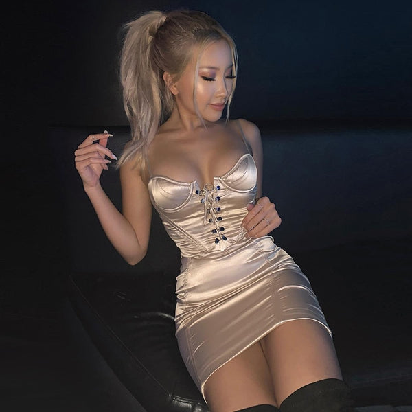 front view of lady wearing a champagne color satin dress featuring a V-neckline with lace-up detail and adjustable shoulder straps.