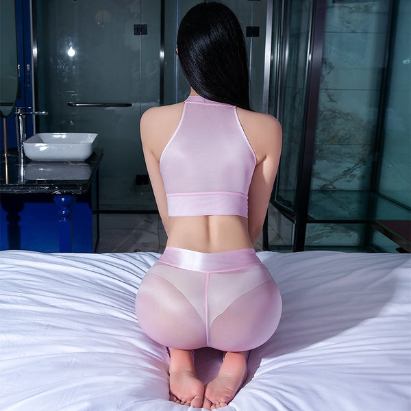 back view of lady wearing pink seductive outfit featuring a crop top with keyhole opening, see through shiny fabric, matching legging with front to crotch zipper closure.