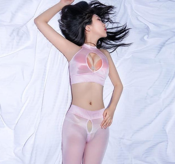 front view of lady wearing pink seductive outfit featuring a crop top with keyhole opening, see through shiny fabric, matching legging with front to crotch zipper closure.
