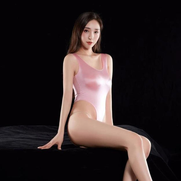 Pink wet look bodysuit featuring a scoop neckline, thick shoulder straps, arousing smooth to the touch fabric, high cut sides and a thong cut back.