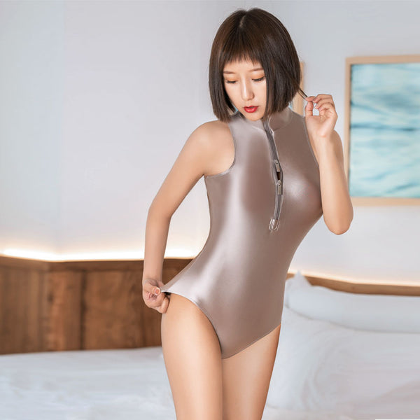 front view of lady wearing a champagne  wet look bodysuit featuring a high neckline, a front zipper closure, and a cheeky cut back.