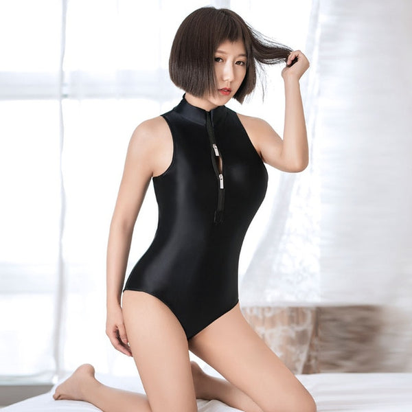 front view of lady wearing a black  wet look bodysuit featuring a high neckline, a front zipper closure, and a cheeky cut back.