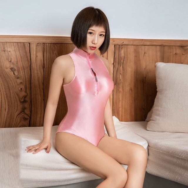 front view of lady wearing a pink  wet look bodysuit featuring a high neckline, a front zipper closure, and a cheeky cut back.