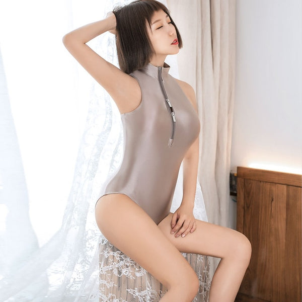 front side view of lady wearing a champagne  wet look bodysuit featuring a high neckline, a front zipper closure, and a cheeky cut back.